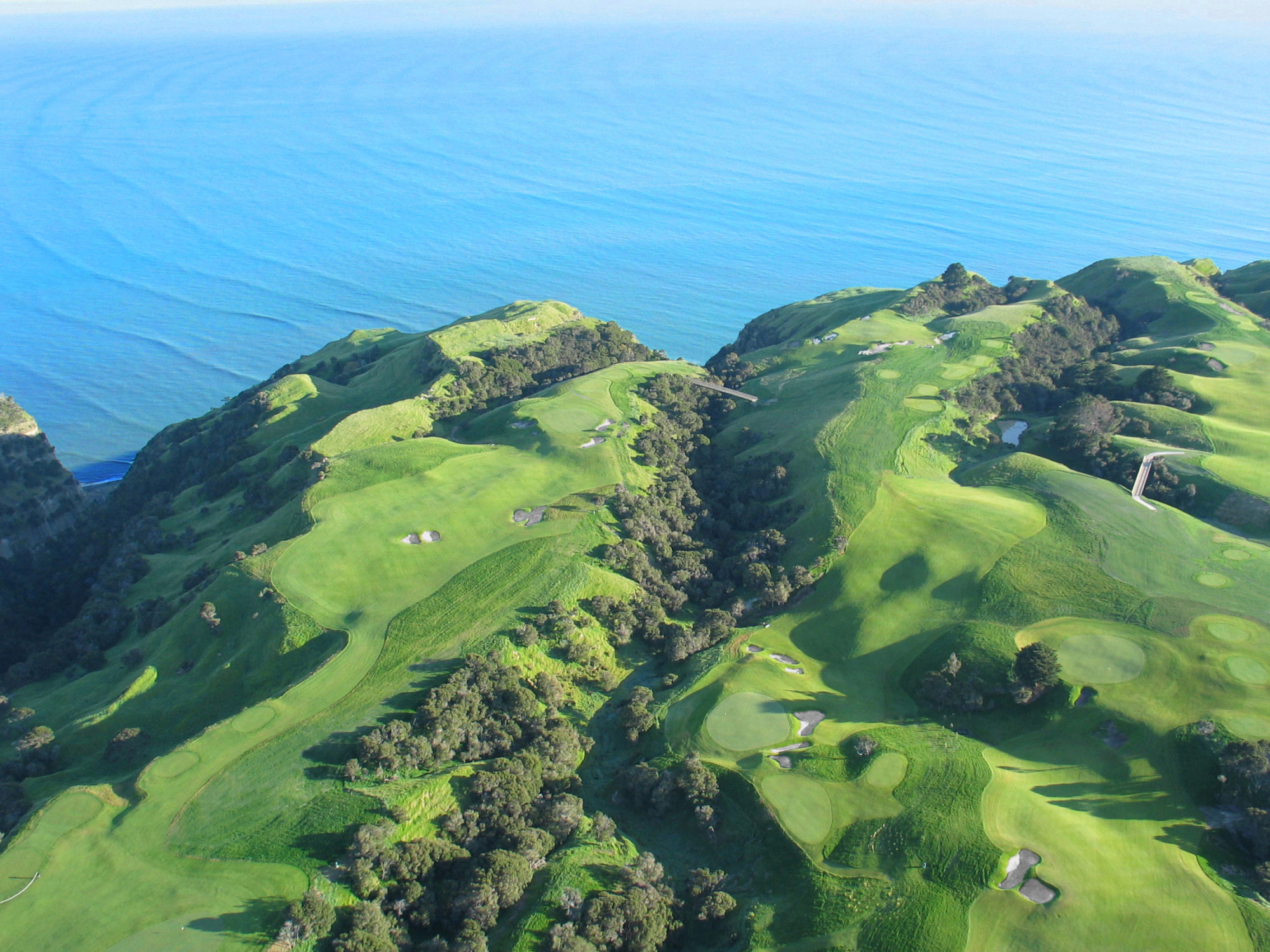 Golfers are so jaded by the aerial photos of Cape Kidnappers that some say they're disappointed when they finally get there. That's the 5th hole playing out toward the water on the left, the par-3 6th playing over the chasm nearest the ocean, and the par-4 7th playing back inland, with its second shot down into a ravine.