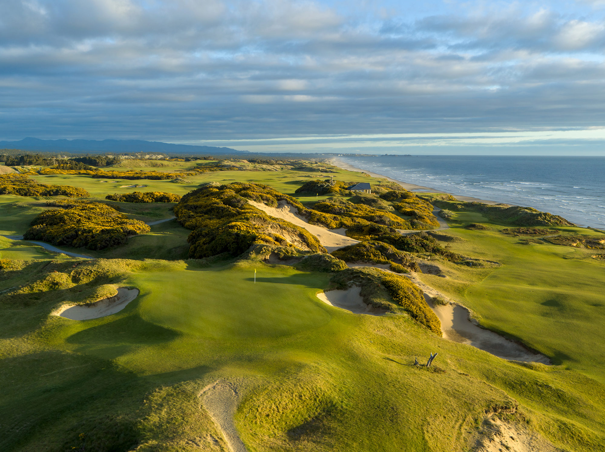 Late afternoon light on the short par 3 14th hole of Pacific Dunes.  A wonderful Tom Doak design at Bandon Dunes Golf Resort in Oregon and one of the top golf destinations in the world.  Beautiful Bandon Dunes photography by Evan Schiller